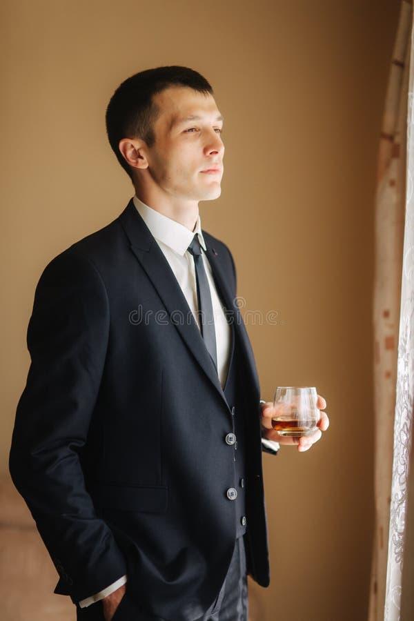 Mannstand von Seite zu Fenster und drind ein wiskey lizenzfreie stockbilder