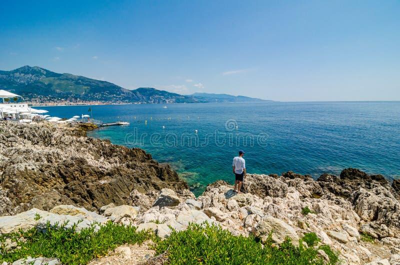 Mannstellung auf steiniger Klippe durch azurblaues Meidterranean-Meer in Roquebrune-Kappe Martin in Frankreich lizenzfreies stockbild