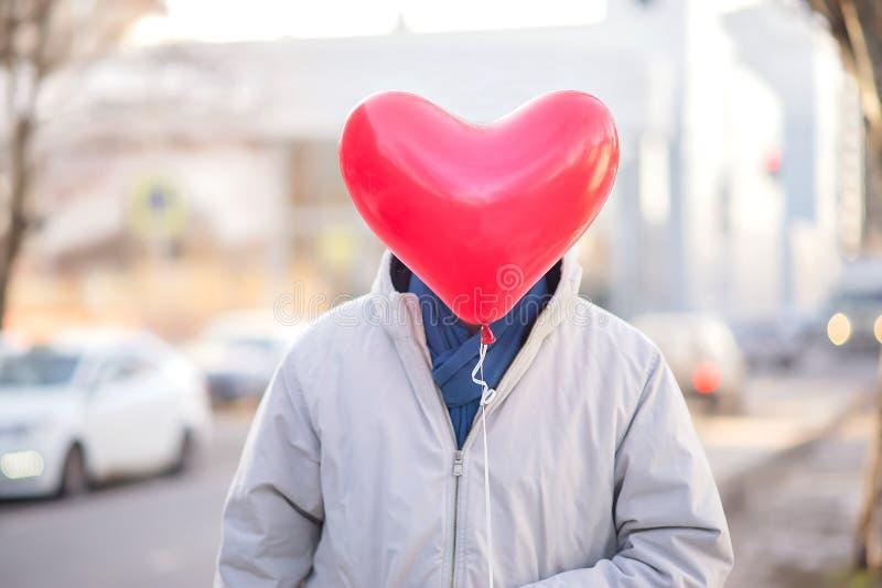 Mannstellung in der Straße und im versteckenden Gesicht hinter dem roten Luftballon geformt als Herz Romanze und des Datums Konze stockbilder