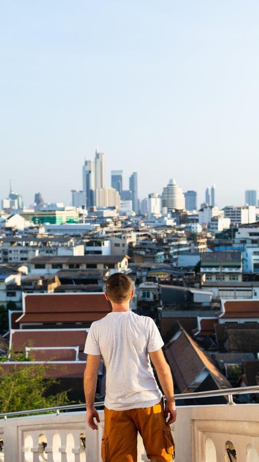 Mannstellung an der Treppe des goldenen Bergtempels, der die Stadt von Bangkok, Thailand übersieht lizenzfreies stockfoto
