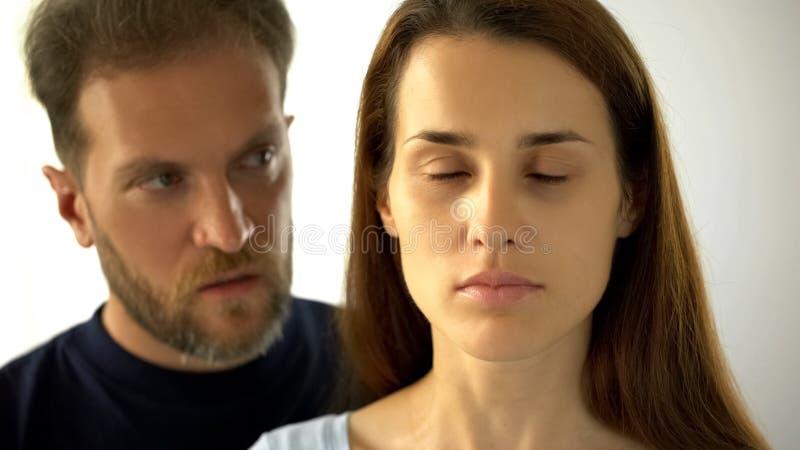 Mannstellung hinter Frau, traurige Dame mit geschlossenen Augen Ehemannentscheidungen hörend stockfoto