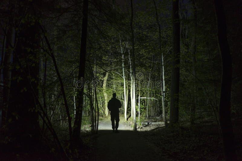 Mannstellung im Freien nachts dunkles gl?nzend mit Taschenlampe stockbild