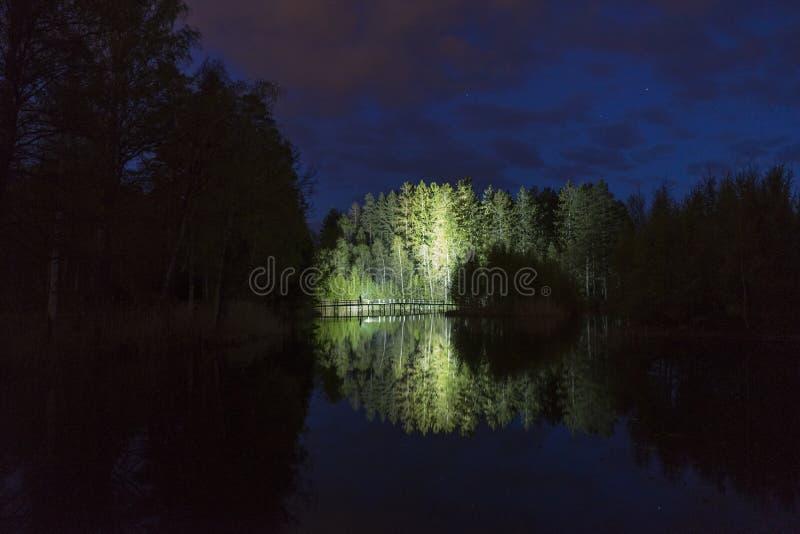 Mannstellung im Freien nachts dunkles gl?nzend mit Taschenlampe lizenzfreies stockfoto
