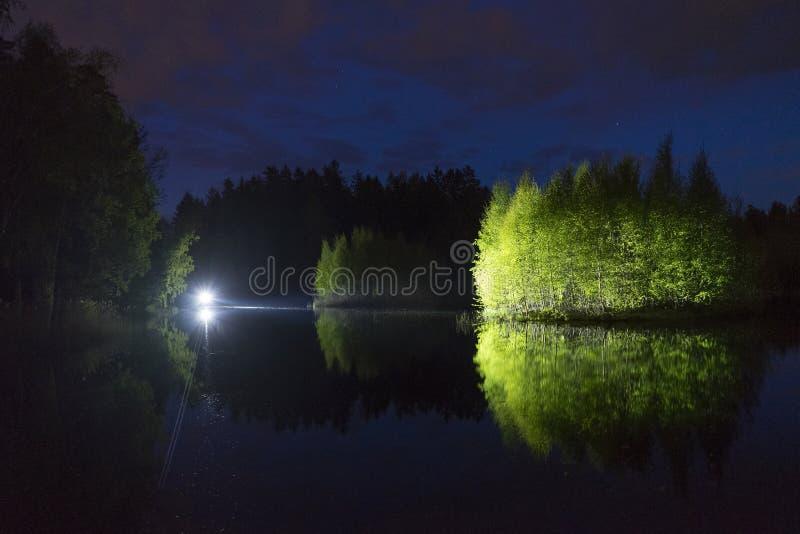 Mannstellung im Freien nachts dunkles gl?nzend mit Taschenlampe stockfotos