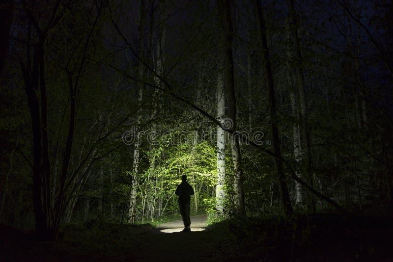 Mannstellung im Freien nachts dunkles gl?nzend mit Taschenlampe lizenzfreies stockbild