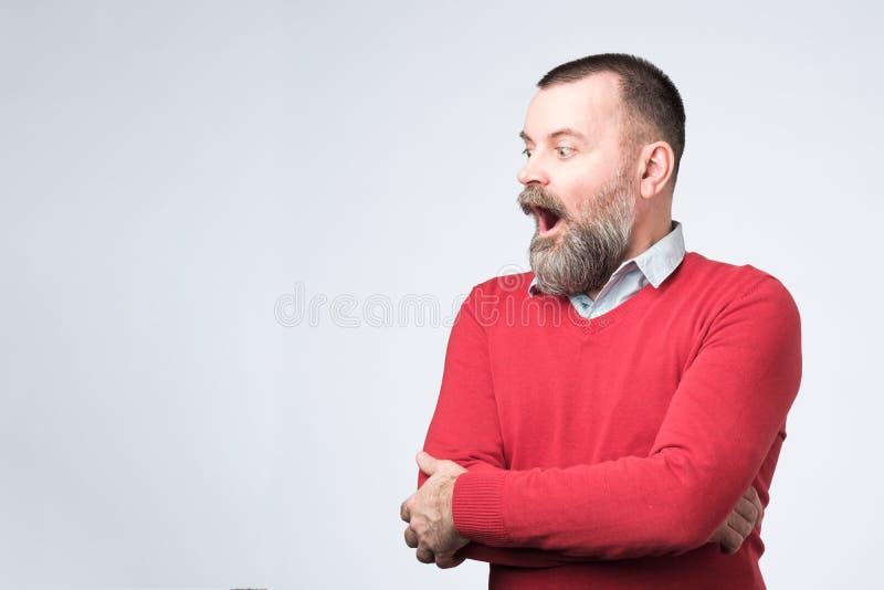 Mannstellung mit dem offenen Mund, der beiseite schaut lizenzfreies stockfoto