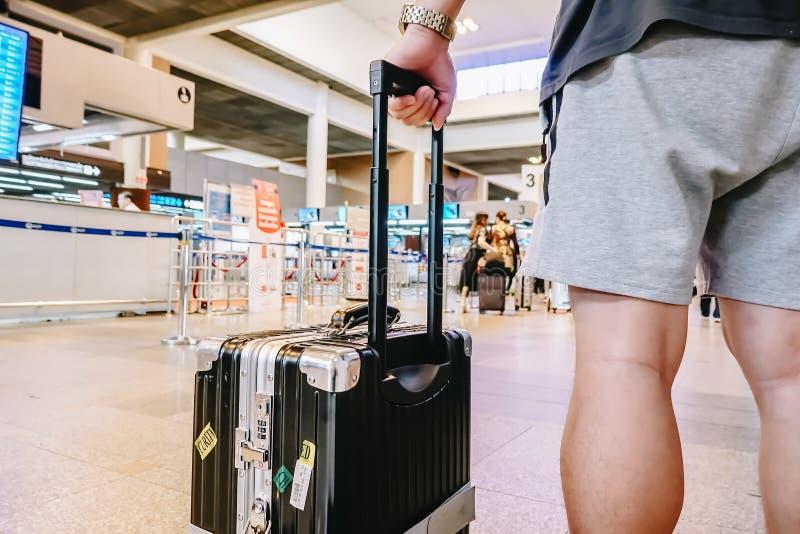 Mannstellung mit Gepäck am Flughafen Mann, der den Aufenthaltsraum betrachtet Flugzeuge bei der Aufwartung auf Einstiegtor betrac stockbild