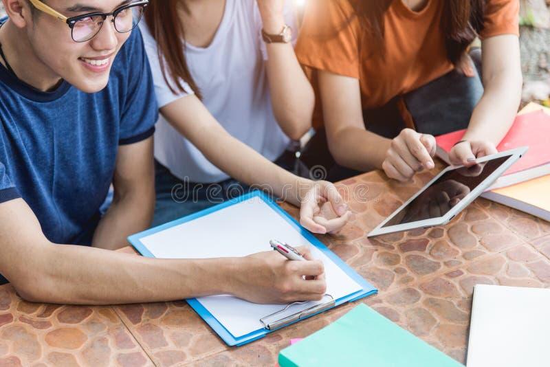 Mannstudenten und -freundin sind konsultieren Informationen vom Computerlaptop, -tablette und -buch, die im Freien sind lizenzfreie stockbilder