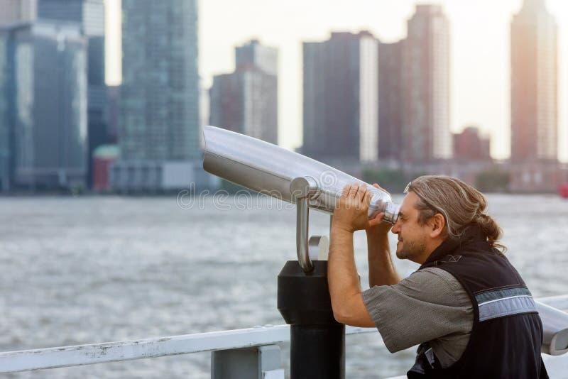 Manntourist, der durch Ferngläser schaut auf New York Freedom Tower, das schöne Stadtlandschaftsreise genießt und lizenzfreie stockfotos