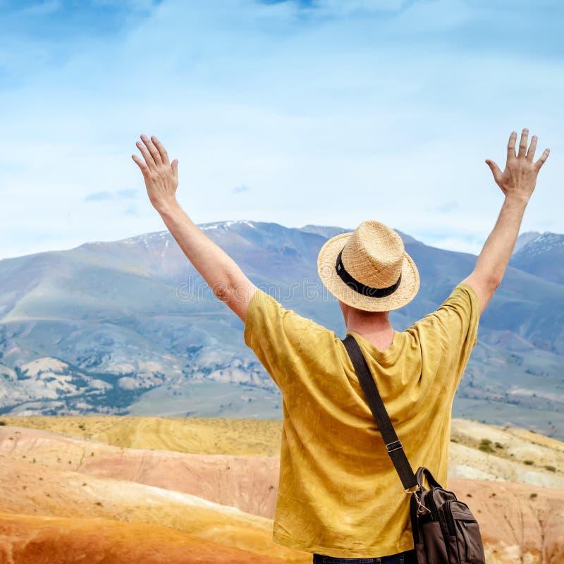 Manntourist in einem Hut betrachtet Altai-Berglandschaft lizenzfreie stockbilder