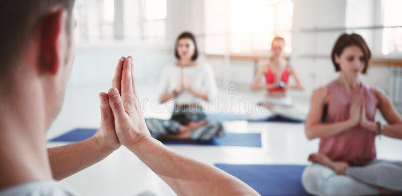 Manntrainer bildet Frauengruppeyogaübungen für Instandhaltungsgesundheitswesen in der weißen Klasse aus Leute zusammen practis Yo lizenzfreie stockbilder