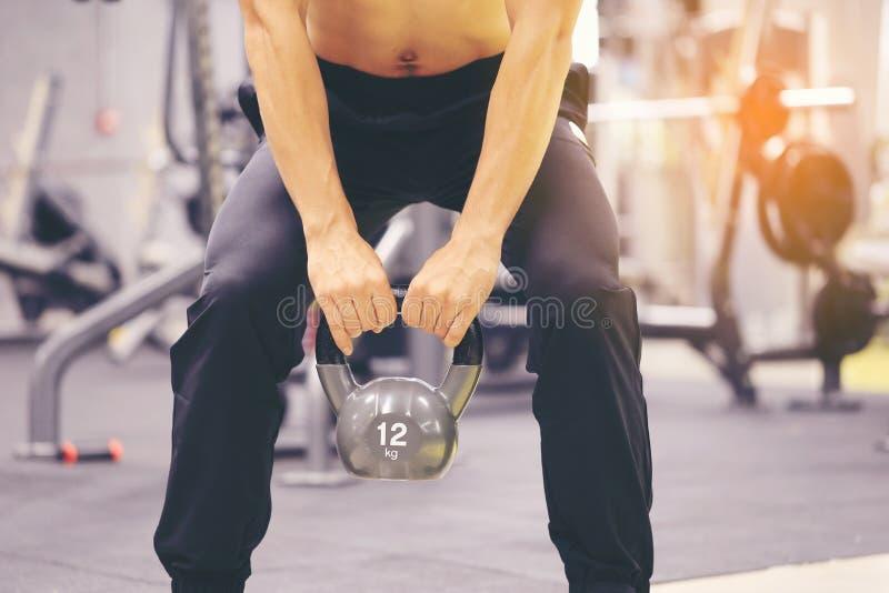 Manntrainingshand, die kettlebell für Brandfett im Körper in der Sportturnhalle, im gesunden Lebensstil und im Sportkonzept hält lizenzfreie stockfotografie