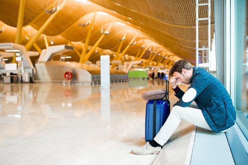 Mannumkippen, traurig und verärgert am Flughafen sein Flug wird verzögert stockbilder