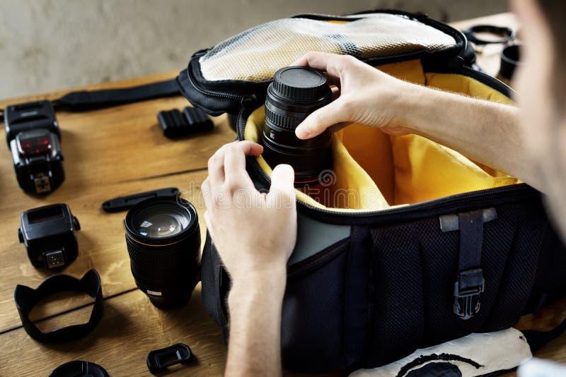 Mannverpackungs-Kameraobjektiv zu seiner Tasche lizenzfreie stockfotos