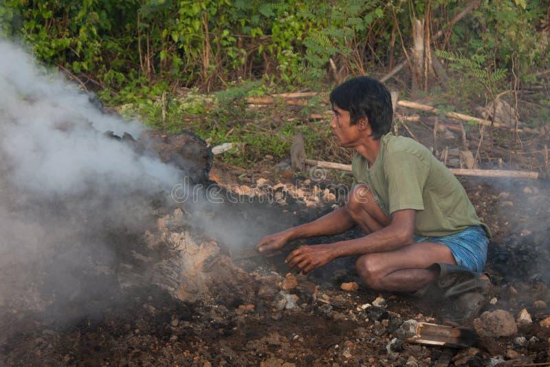 Mannversuch zu ignit Kohle lizenzfreie stockfotos