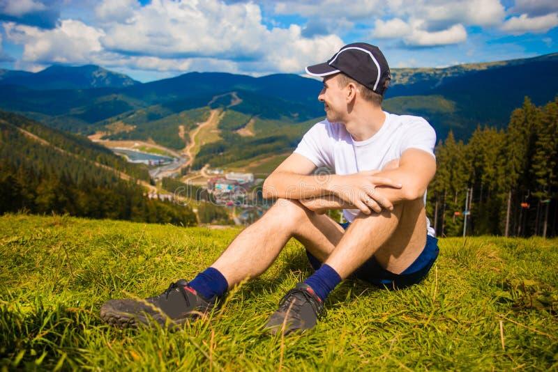 Mannwanderer, der auf Hügel sich entspannt und schöne Gebirgstalansicht in Sommer bewundert stockbild