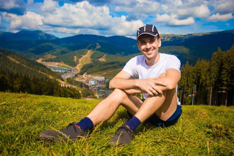 Mannwanderer, der auf Hügel sich entspannt und schöne Gebirgstalansicht in Sommer bewundert lizenzfreie stockbilder