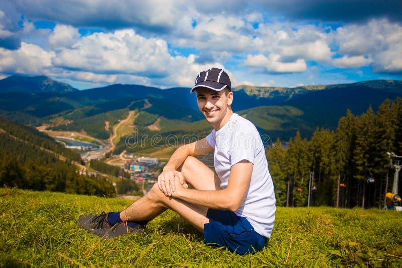 Mannwanderer, der auf Hügel sich entspannt und schöne Gebirgstalansicht in Sommer bewundert stockfotos