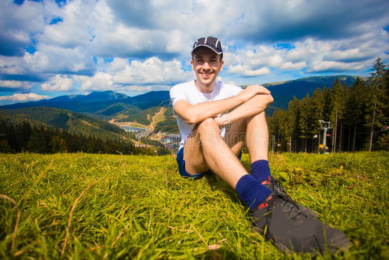 Mannwanderer, der auf Hügel sich entspannt und schöne Gebirgstalansicht in Sommer bewundert stockbilder