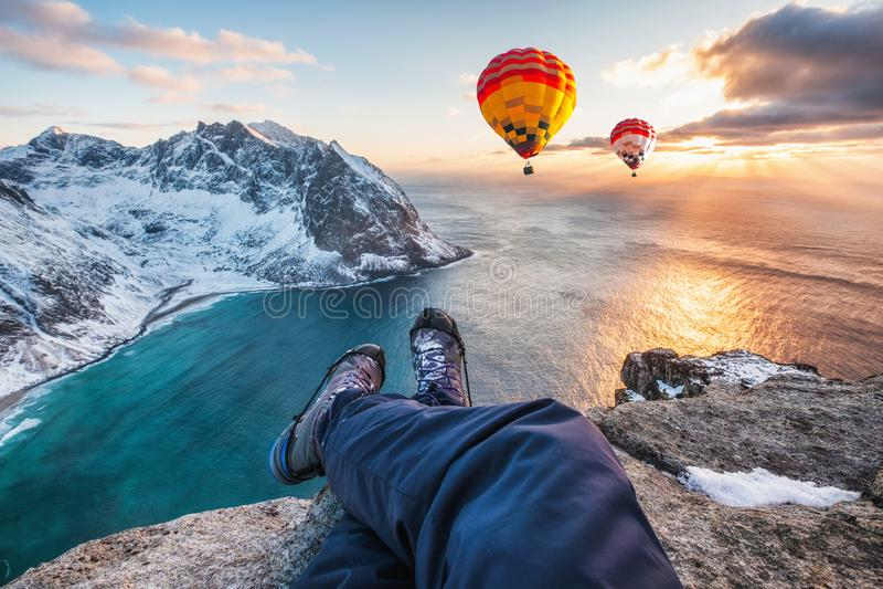 Mannwanderer-Querbeine, die auf Felsenkante mit Heißluftballonfliegen auf Ozean sitzen lizenzfreies stockfoto
