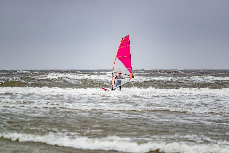 Mannwindsurfen am bewölkten windigen kalten Tag lizenzfreies stockbild