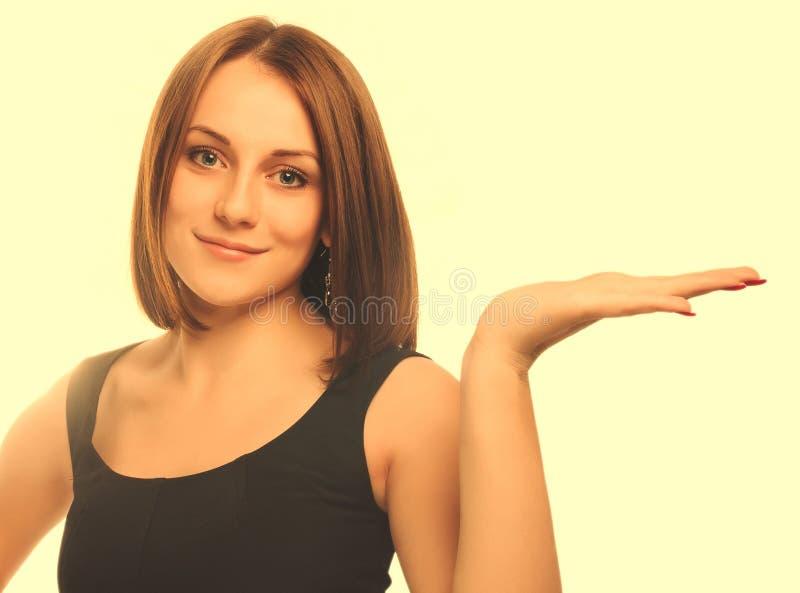 Mano abierta de la demostración rubia joven feliz de la mujer del retrato que se sostiene en el bl fotografía de archivo