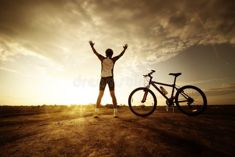 Mano abierta del hombre de la silueta con la bicicleta fotografía de archivo