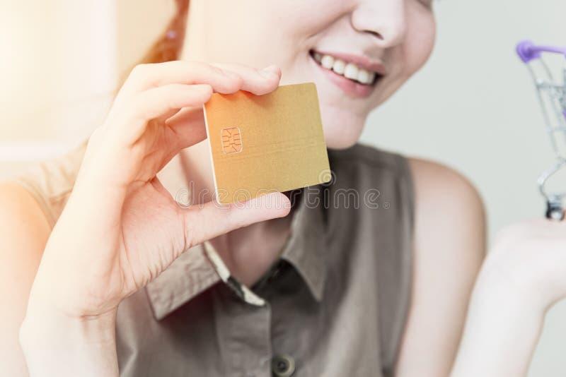 Mano adolescente de la muchacha del primer usando tarjeta de crédito fotografía de archivo