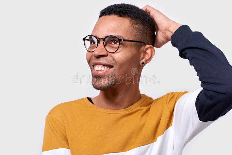Mano africana pensativa feliz de la tenencia del hombre en la cabeza que sonríe y que mira el espacio en blanco de la copia fotos de archivo libres de regalías