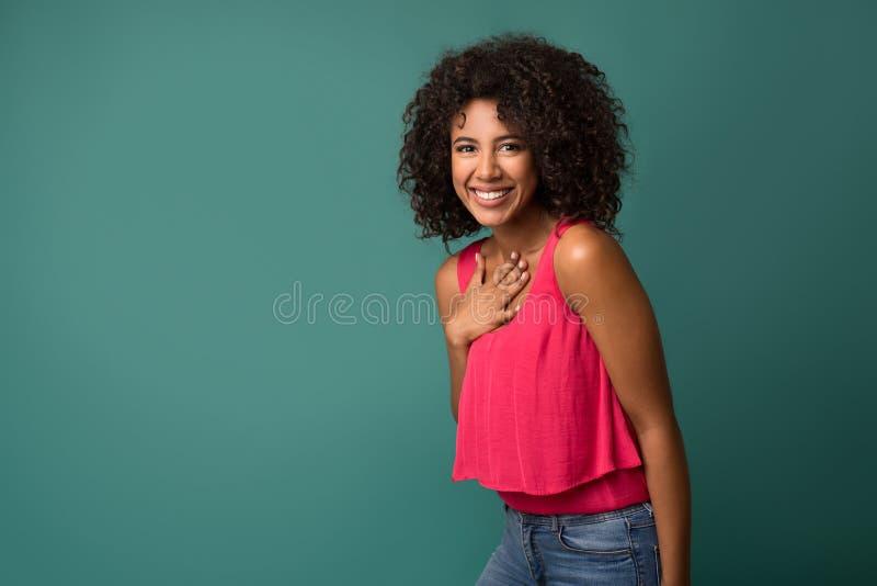 Mano afroamericana allegra della tenuta della donna sul petto immagine stock