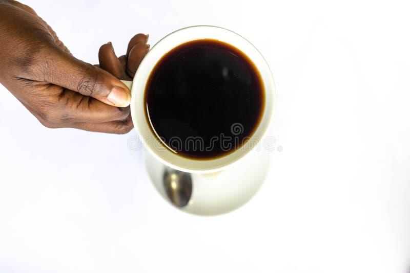 Mano afroamericana della donna una che tiene una tazza di caffè bianca Mani femminili nere che tengono una tazza di caffè calda c immagine stock libera da diritti