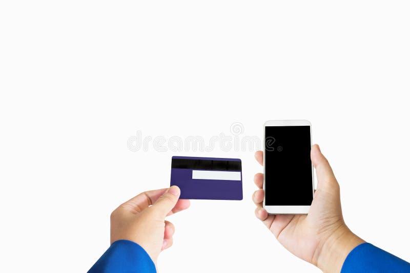 Mano aislada con tarjeta de cajero automático del crédito o del debe y el teléfono elegante o m imagen de archivo libre de regalías