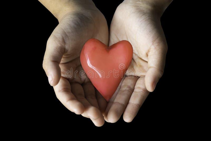 Mano aislada que lleva a cabo un corazón rojo de la forma del caramelo en un backgro negro fotografía de archivo libre de regalías