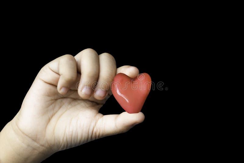 Mano aislada que lleva a cabo un corazón rojo de la forma del caramelo en un backgro negro imagenes de archivo