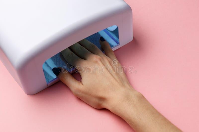 Mano alle luci UV della lampada per i chiodi su fondo rosa concetto creativo minimo Fondo rosa fotografie stock libere da diritti