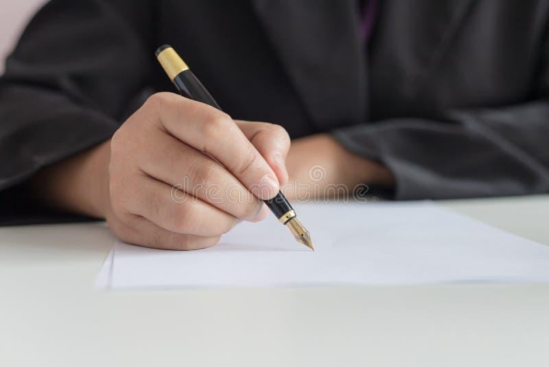 Mano alta vicina del colpo della donna di affari facendo uso della penna da scrivere sulla profondità di campo bassa del fuoco sc royalty illustrazione gratis