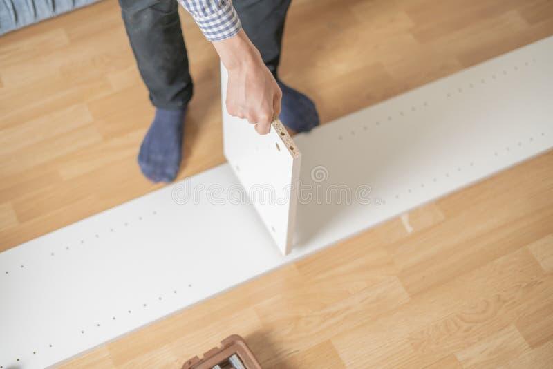 Mano alta vicina del lavoratore che monta la nuova mobilia sul pavimento di legno nella nuova h piana fotografia stock