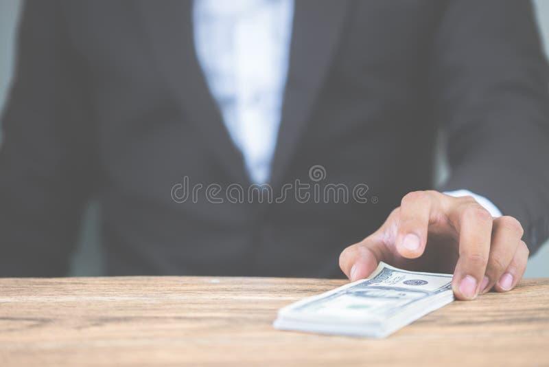 Mano alta vicina dell'uomo d'affari che tiene le banconote in dollari dei soldi sulla tavola di legno Usando come concetto di cor fotografia stock