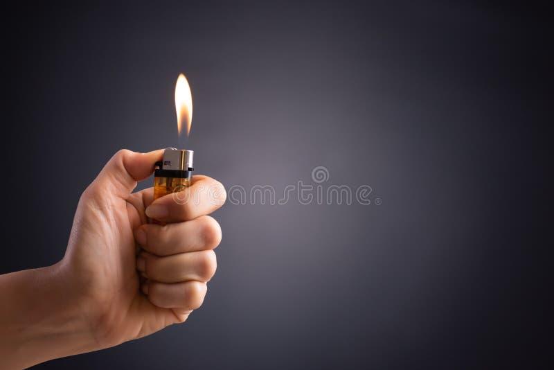 Mano alta vicina della donna che tiene un accendino bruciante nei precedenti scuri fotografia stock
