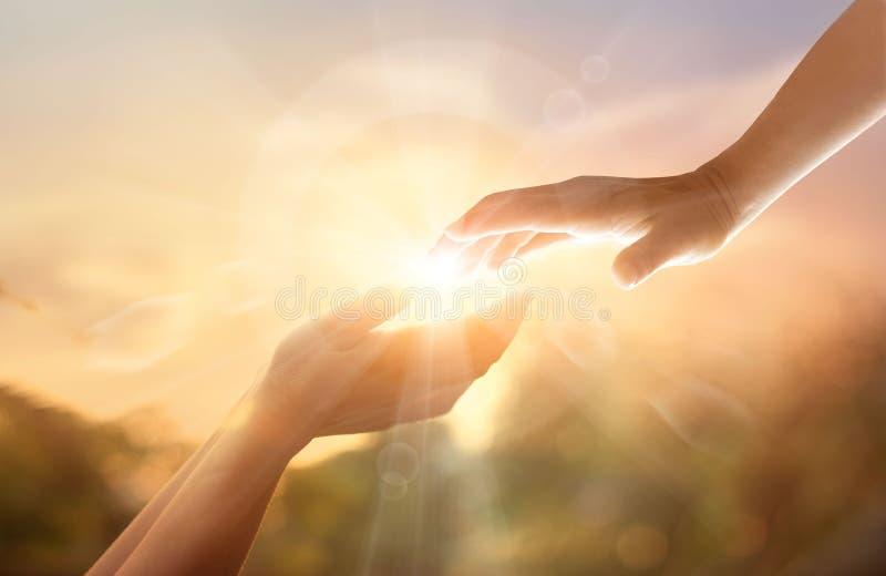 Mano amiga del ` s de dios con la cruz blanca en fondo de la puesta del sol DA fotos de archivo