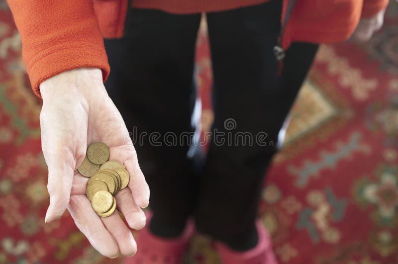 Mano anziana che tiene il risparmio di pensione del rame di penny delle monete degli spiccioli dei contanti dei soldi immagine stock