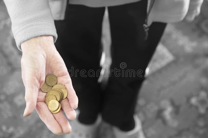 Mano anziana della società difficile della persona senior in pieno delle monete bronzee senza valore immagini stock