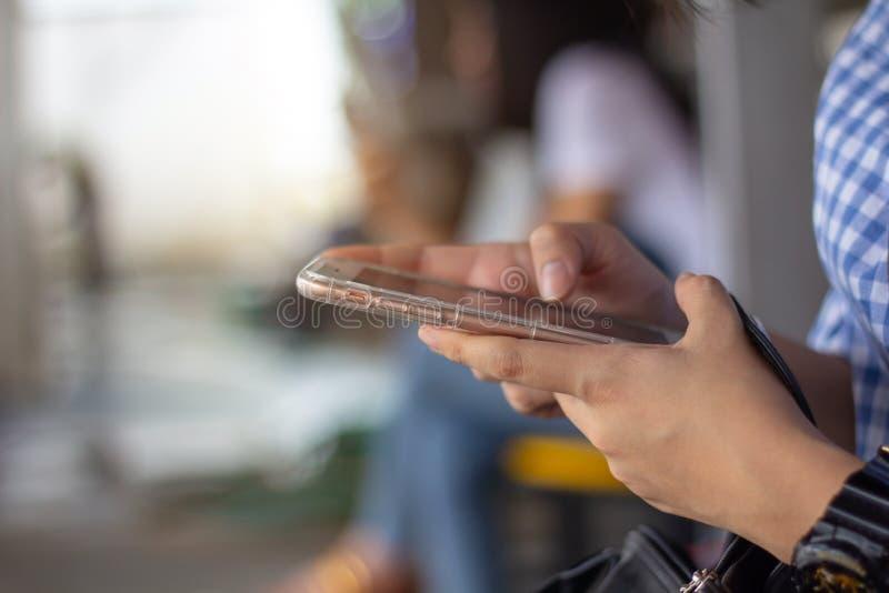 Mano ascendente cercana de la mujer usando vista lateral del aire libre elegante del teléfono fotografía de archivo