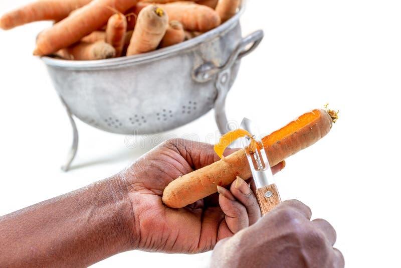 Mano ascendente cercana de las zanahorias de la c?scara de la mujer con un cuchillo en el cuarto de la cocina en blanco imágenes de archivo libres de regalías