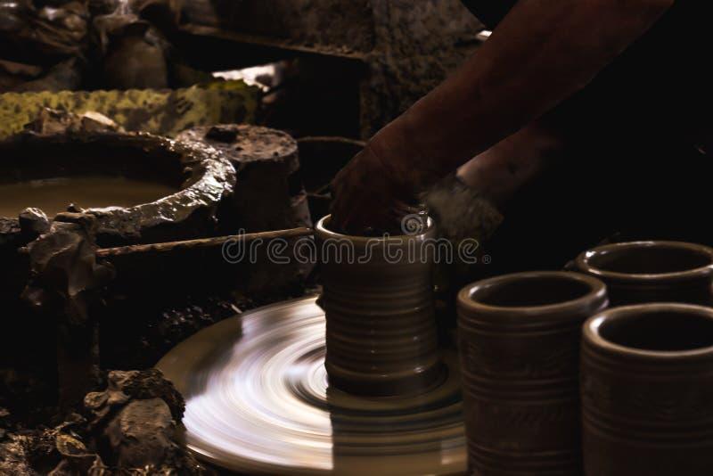 Mano ascendente cercana del alfarero hacer un estilo tailandés del florero de la arcilla en una rueda de alfarero en pueblos de l fotografía de archivo libre de regalías