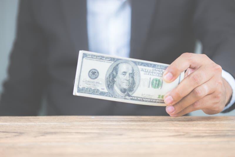 Mano ascendente cercana del hombre de negocios que lleva a cabo billetes de d?lar del dinero en la tabla de madera Usando como co imagen de archivo libre de regalías