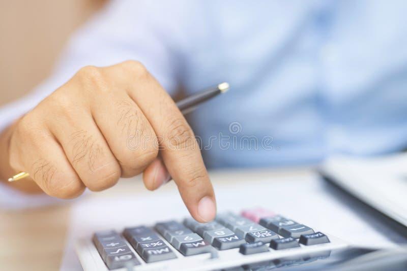 Mano ascendente cercana del hombre de negocios usando la calculadora y la escritura en un cuaderno fotos de archivo