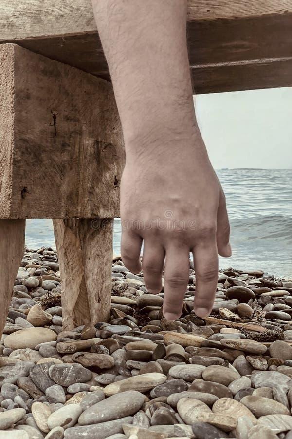 Mano ascendente cercana del hombre que cuelga de un banco, de los guijarros y del mar de la playa en fondo Atmósfera del agotamie imágenes de archivo libres de regalías