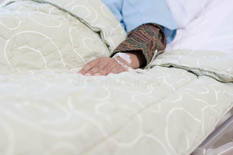 Mano ascendente cercana del paciente con la infusión en cama cómoda de la clínica dentro del sitio de hospital fotografía de archivo