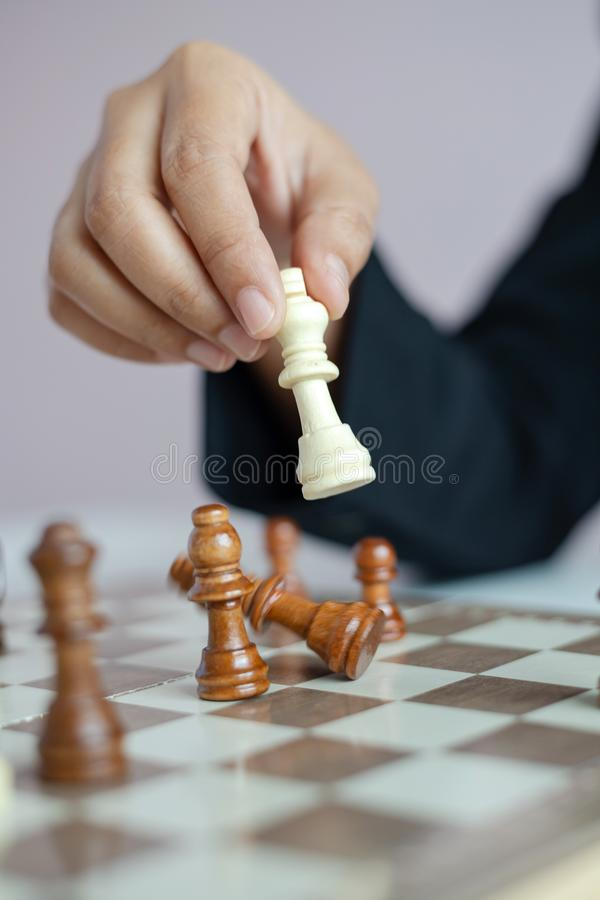 Mano ascendente cercana del tiro de la mujer de negocios que juega al tablero de ajedrez para ganar matando al rey de la competen fotos de archivo libres de regalías